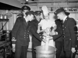 The officers and wardroom cook mixing the Christmas Pudding on board HMS HOWE.