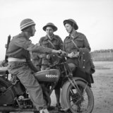 L/Cpl E Martin of the Corps of Military Police sits astride his motorcycle and chats to Cpl Joyce Collins and L/Cpl Celia Strong, ATS clerks at 21st Army Group HQ, Normandy, 28 July 1944.