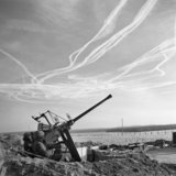 The crew of a Bofors anti-aircraft gun view vapour trails in the sky high above the Dutch-German border near Brunssum, 25 December 1944.