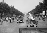An AFPU (Army Film and Photographic Unit) jeep displaying a large union flag drives down the Champs Elysees in Paris, 26 August 1944.