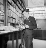 Phillip Fricker, a Flight Sergeant in the Air Training Corps (ATC), studies a book on air navigation in a bookshop in his home town of Dartford in Kent, 26 April 1942.