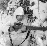 A 6th Airborne Division sniper on patrol in the Ardennes, wearing a snow camouflage suit, 14 January 1945.