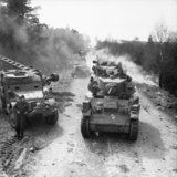 Stuart light tanks pass half-tracks and other vehicles of 15th (Scottish) Division during the advance to the River Elbe, Germany, 13 April 1945.