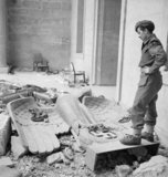 Sergeant R S Baker of the Army Film & Photographic Unit (AFPU) looks at a fallen Nazi eagle and swastika amidst the ruins of Hitler's Reich Chancellery in Berlin, 3 July 1945.