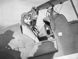 Pauline Gower, Commandant of the Air Transport Auxiliary Women's Section, waving from the cockpit of a de Havilland Tiger Moth at Hatfield, Hertfordshire, prior to a delivery flight, 10 January 1940.