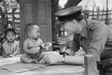 Squadron Leader Joseph Heaven, an RAF Methodist Chaplain, plays with a baby in a village near Monywa in Burma, March 1945.