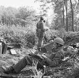 War Correspondent Alan Wood is seen typing his despatch, while Airborne troops in the background consult a map during Operation 'Market Garden', Holland, 18 September 1944.