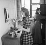 A female war worker fixes her hair in the bedroom she shares with another worker at the hostel attached to the Royal Ordnance Factory, Bridgend, in January 1942.