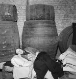 An old woman sleeps in a bed constructed on top of a row of barrels in the cellar of a wine merchant's in the East End of London, 1940.