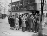 Mrs Ridley (fourth left) queues for a bus that will take her from her workplace in the City to her evening class in the West End of London, 1940.