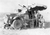 Officers of the 11th Hussars in a Morris CS9 armoured car use a parasol to give shade while out patrolling on the Libyan frontier, 26 July 1940.