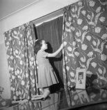 Doreen Buckner draws the curtains in her family's London home to comply with the nightly 'Blackout' during the Second World War.
