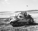 Sherman Mk III tank of the Indian Armoured Corps, with infantry of the Bombay Grenadiers aboard, training in the Middle East, March 1944.