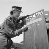 Private Margaret Hicks of the Auxiliary Territorial Service (ATS), serving with a mixed anti-aircraft battery on the South Coast, paints another V-1 flying bomb 'kill' on the battery scoreboard, 6 August 1944.