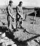 Two soldiers visit the Military Cemetery at Kohima to pay their respects to their former comrade Lance Corporal John Harman VC, 1945.