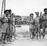 Troops from 6th Armoured Division gather round a road sign during the advance on Tunis, 6 May 1943.