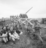 Auxiliary Territorial Service (ATS) girls watch a tug-of-war contest during a sports competition at a mixed 4.5-inch anti-aircraft battery near Edinburgh, 30 July 1943.
