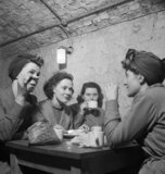 Women war workers enjoy tea and sandwiches in the canteen of aN underground factory at New Brighton, on the Wirral, 1945.