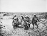 A team of stretcher bearers struggle through deep mud to carry a wounded man to safety near Boesinghe on 1 August 1917 during the Third Battle of Ypres.