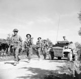 British Infantry move up past a Daimler scout car during the advance of 78th Division, Italy, 30 June 1944.