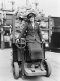 A female employee of the Great Eastern Railway Company driving a battery powered rail parcel truck during the First World War.