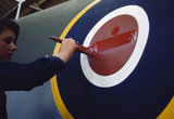 A young woman worker painting the fuselage roundel on a Mosquito aircraft at de Havilland's factory at Hatfield in Hertfordshire, 1943.