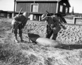 Troops examine an unexploded German bomb at the railway station at Grong, near Namsos, April 1940.