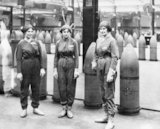 Female munitions workers stand in front of 15-inch high explosive shells at the National Shell Filling Factory at Chilwell, Nottinghamshire.