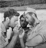 Men of the Long Range Desert Group relax with cigarettes after returning to headquarters at the end of a desert patrol, Siwa, Libya, 1942