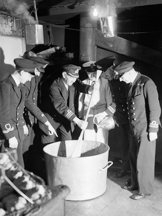 The captain of a destroyer depot ship in the Home Fleet at Scapa Flow stirring the Christmas pudding, while the First Lieutenant adds a tot of rum, 12 December 1942.