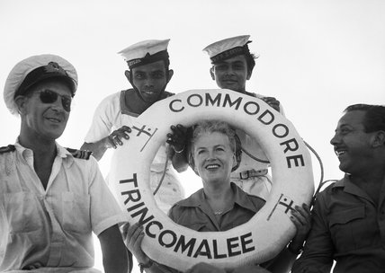 Gracie Fields poses with a group of sailors in Trincomalee Harbour, Ceylon, during a visit to the British East Indies Fleet, 20 October 1945.
