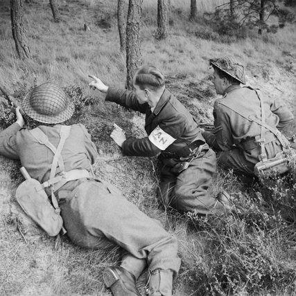 A member of the PAN (Partisan Action Netherlands) guides British troops to German positions near Valkenswaard, 25 September 1944.