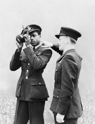 Pilot Officer J H Smythe of Sierra Leone, a newly-qualified navigator, being instructed in the use of the sextant by an instructor at No. 11 Operational Training Unit, Westcott in Buckinghamshire, 1 August 1943.