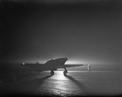 A Hawker Hurricane Mk I of No. 85 Squadron taxiing by the light of a flare at Debden, before taking off to intercept night raiders, 14 March 1941.