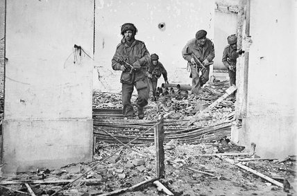 British airborne troops moving through a shell-damaged house in Oosterbeek near Arnhem during Operation 'Market Garden', 23 September 1944.