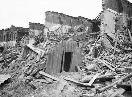 An Anderson shelter remains intact amidst destruction in Latham Street, Poplar, London during 1941.