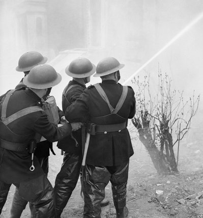 Firemen of the National Fire Service tackle a blaze in a house during a Civil Defence exercise in Fulham, London during 1942.