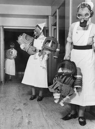 Nurses carry babies during a gas drill in a London hospital during 1940.