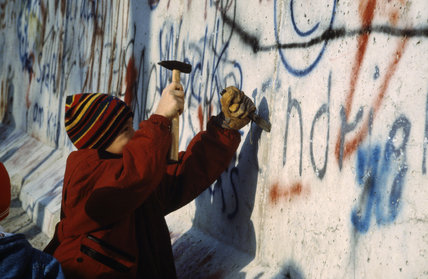 A child using a hammer and chisel to remove a piece of the Berlin Wall after its opening by the East German Government on 9 November 1989.