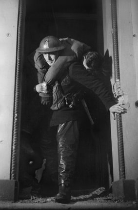 Auxiliary Fireman Brian Gilks carries a casualty as he leaves a bomb-damaged building during a 'shout' somewhere in London during 1940.