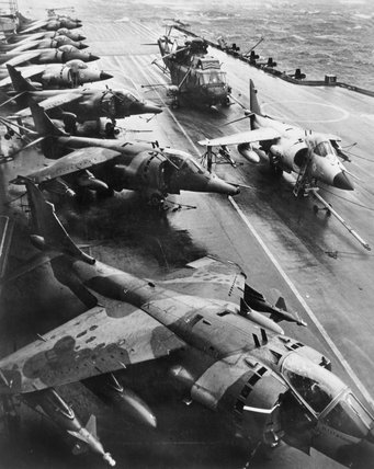 British Aerospace Harrier GR.3s of No. 1 Squadron RAF and Royal Navy Sea Harrier FR.1s on the flight deck of HMS HERMES during the deployment to the Falkland Islands, 19 May 1982.