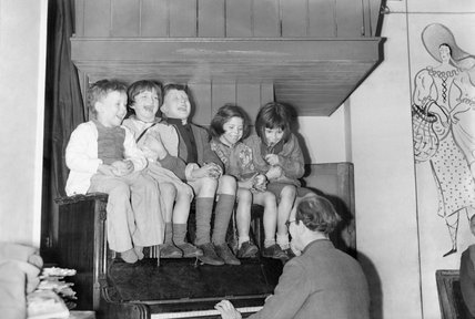 At a Save the Children club on Eversholt Street, London, during 1944, children sit on the piano being played by one of the club warden's.
