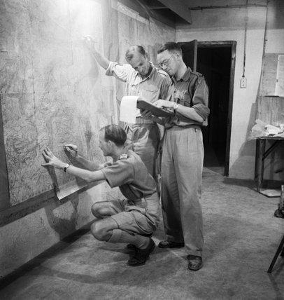 Staff officers plotting troop positions during the invasion of Sicily on a wall map in the underground operations room at Malta, 9 July 1943.