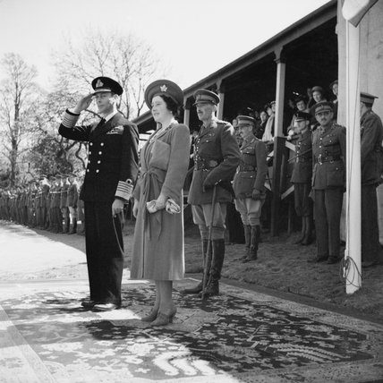 HM King George VI and Queen Elizabeth take the salute at a march past of troops in the UK, 6 May 1942.
