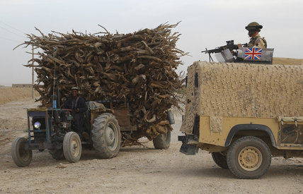 A civilian driving a tractor loaded with wood passes a British Army landrover in Lashkar Gah, part of the Provincial Reconstruction Team in Helmand, Afghanistan, 3 May 2006.