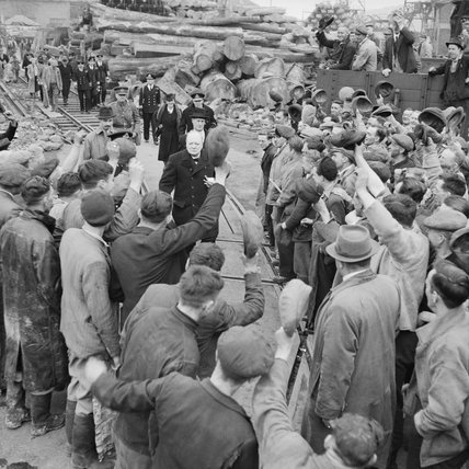 Winston Churchill is cheered by workers during a visit to bomb-damaged Plymouth, 2 May 1941.