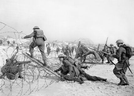 Troops of the 7th Battalion, the Suffolk Regiment, negotiate barbed-wire obstacles during training on the beach at Sandbanks near Poole, 22 March 1941.