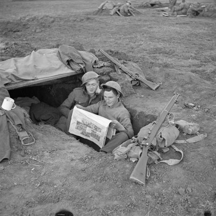 Men of the 2nd Royal Inniskilling Fusiliers read 'Ireland's Saturday Night', a Belfast newspaper, in their foxhole in the Anzio bridgehead, 17 March 1944.