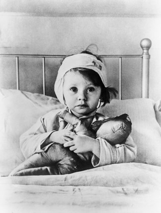 Eileen Dunne, aged three, sits in bed with her doll at Great Ormond Street Hospital for Sick Children, after being injured during an air raid on London in September 1940.