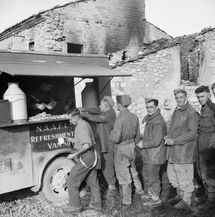 Gunners of 78th Field Regiment, Royal Artillery queuing at a NAAFI refreshment van in Italy, 22 November 1943.
